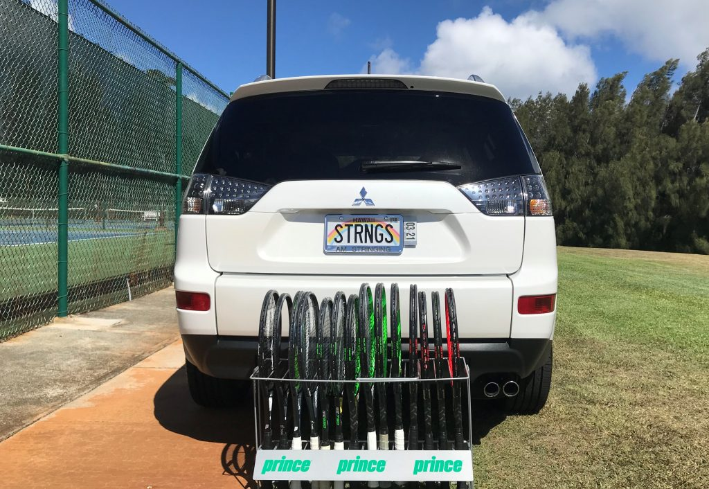 AM Stringing SUV (license plate STRNGS) with a rack of Prince racquets behind it. Illustrating AM Stringing is your source for Prince racquet demos and demo tips.